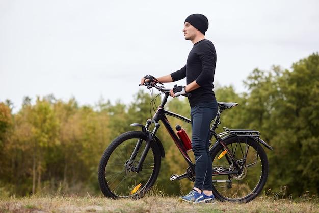 Ciclista deportista activo viste traje negro de pie con bicicletas en una colina cerca de árboles verdes, disfrutando de la vista frente a él