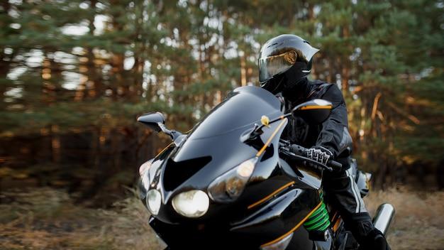 Ciclista deportivo con casco y equipo de protección de cuero en una bicicleta deportiva rápida