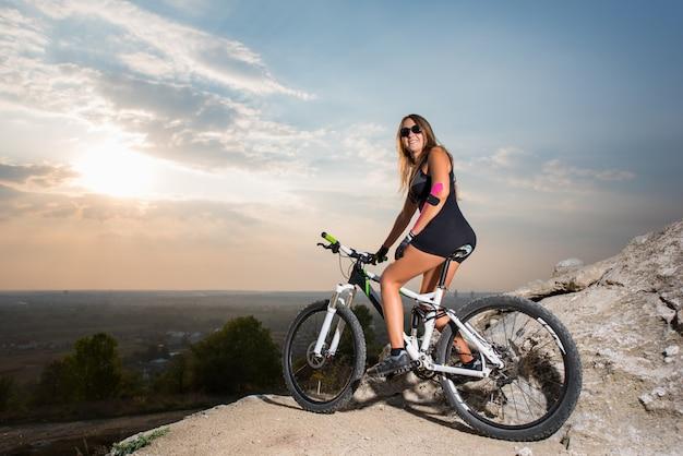 Ciclista descansando en las montañas al atardecer