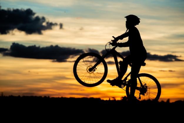 Ciclista descansando silueta al atardecer. concepto activo de deporte al aire libre