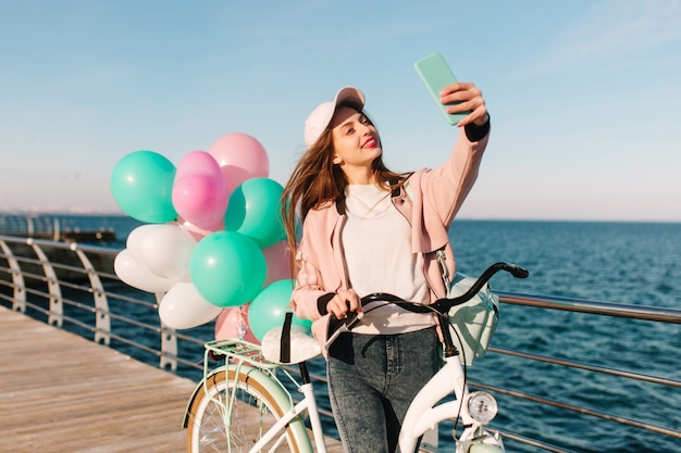 Ciclista encantadora con una gorra rosa y una cazadora sonriendo y tomando selfie en el fondo del mar. adorable chica morena con bicicleta blanca y coloridos globos de fiesta divirtiéndose junto al océano.