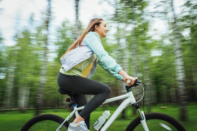 Ciclista feliz de la muchacha que monta en una bici de montaña afuera. viaje de aventura.