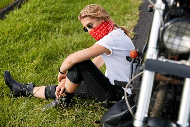 Ciclista femenina sentada sobre el césped junto a la moto