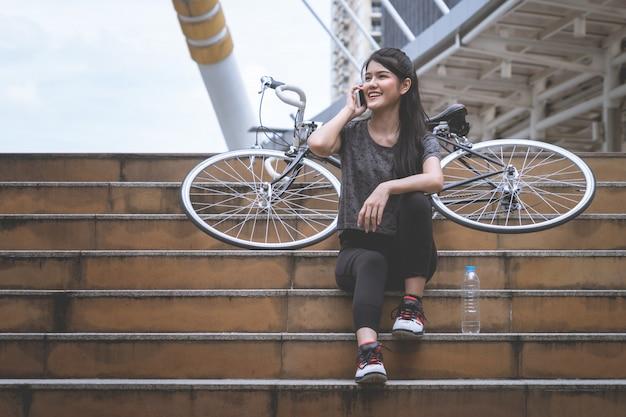 Ciclista femenino está llamando al móvil en una escalera