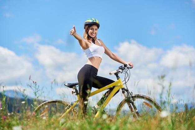 Ciclista femenino sonriente que monta en la bicicleta amarilla en las montañas el día de verano, que muestra los pulgares encima de la muestra contra el cielo azul y las nubes. actividad al aire libre, concepto de estilo de vida. copia espacio