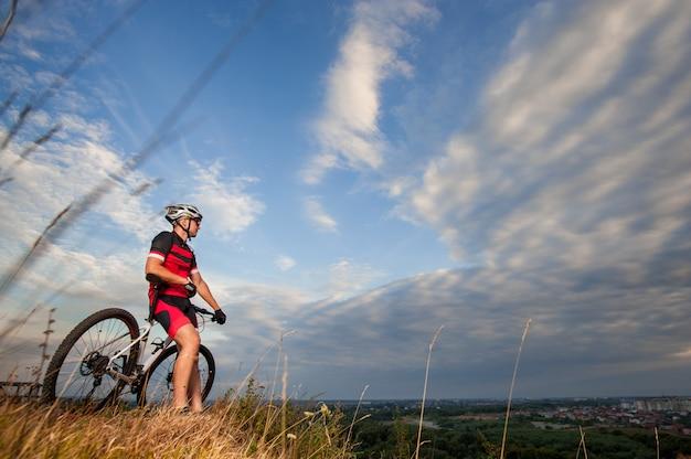 El ciclista de fondo está descansando en la cima de la colina.