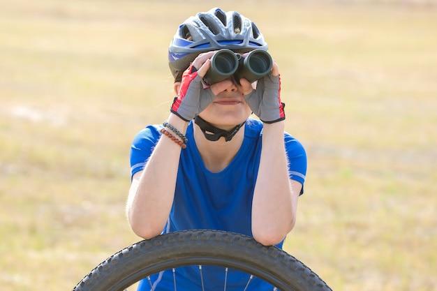 Ciclista hermosa chica mira a través de binoculares