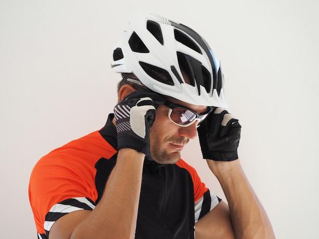 Un ciclista en jersey y casco se pone gafas de sol. retrato de cerca
