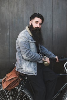 Ciclista joven que se sienta con los auriculares y el bolso que miran la cámara