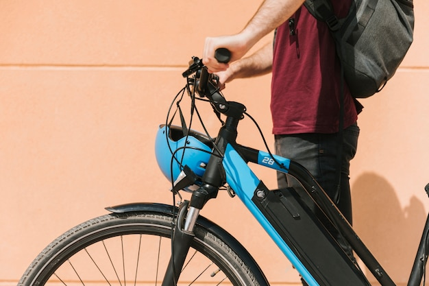 Ciclista lateral de pie junto a la bicicleta eléctrica.