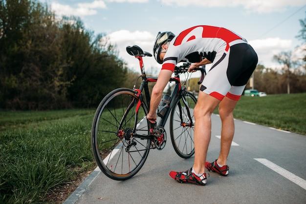 Ciclista masculino en casco y ropa deportiva ajusta la bicicleta antes de la competencia