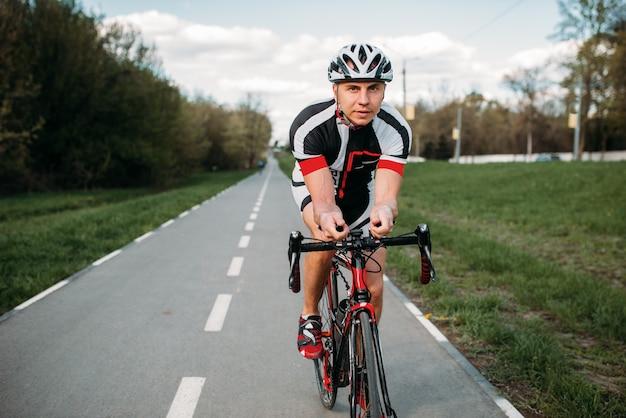 Ciclista masculino en casco y ropa deportiva paseos en bicicleta