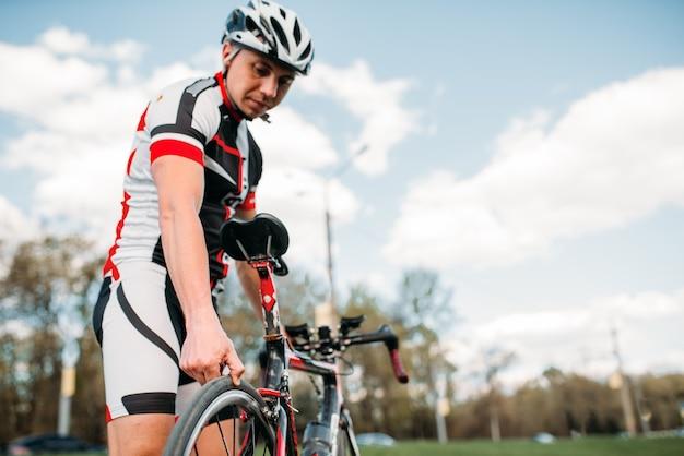 Ciclista masculino en casco y ropa deportiva se prepara antes de la competición de bicicletas.