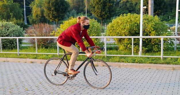 Ciclista masculino elegante joven caucásico en chaqueta casual roja y máscara andar en bicicleta en la calle en la ciudad. concepto de pandemia de coronavirus. hombre guapo en protección respiratoria con paseo en bicicleta.