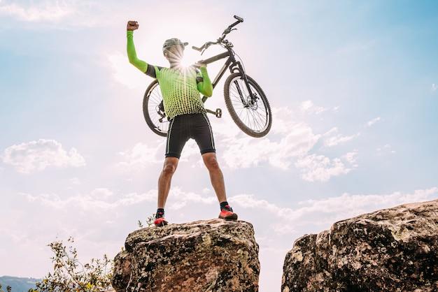 Ciclista masculino emocionado latino que lleva su bicicleta por encima de su cabeza después de terminar de montar en la montaña