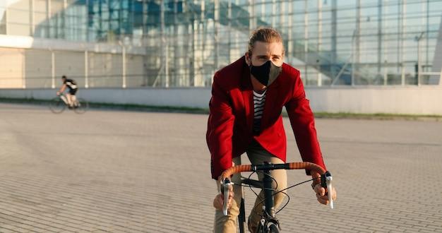 Ciclista masculino con estilo caucásico en chaqueta casual roja y máscara en bicicleta en la ciudad. hombre guapo en protección respiratoria con paseo en bicicleta. edificio moderno de cristal en el fondo. paisaje urbano.