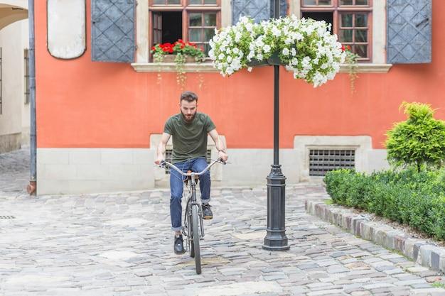 Ciclista masculino joven que monta el pavimento empedrado del guijarro de la bicicleta