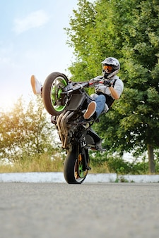 Ciclista masculino practicando acrobacias en bicicleta