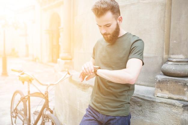 Ciclista masculino que mira tiempo en el reloj de pulsera