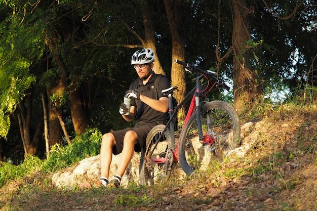 Ciclista masculino sentado en las rocas y el agua potable en el bosque.