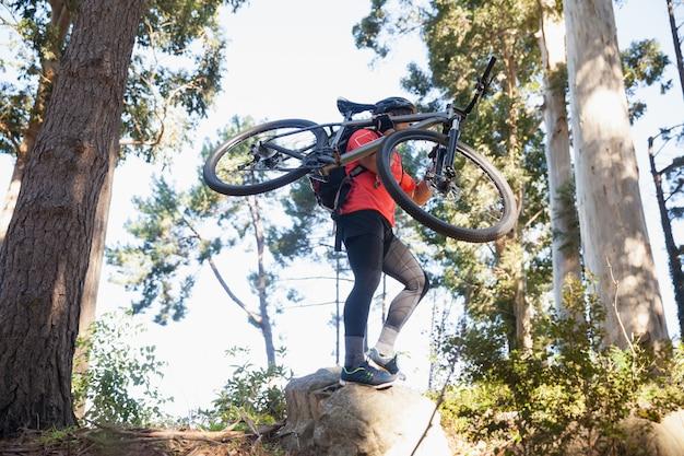 Ciclista de montaña macho llevando bicicleta en el bosque