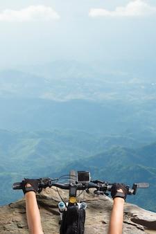 Ciclista de montaña, mujeres montando en un manillar de bicicleta de pie mirando hacia abajo en la cima de una vista a la montaña