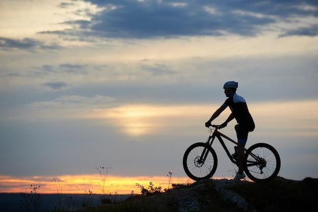 Ciclista montando bicicleta en el crepúsculo.