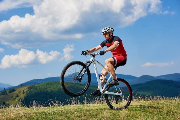 Ciclista montando bicicleta de cross country, girando una rueda de bicicleta en la colina de montaña