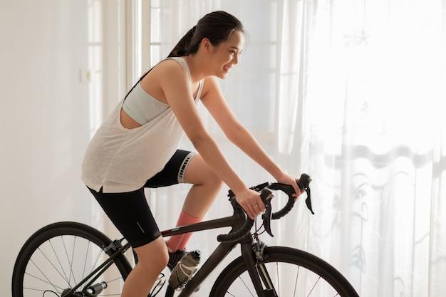 Ciclista mujer asiática. ella hace ejercicio en casa. ella anda en bicicleta en el entrenador