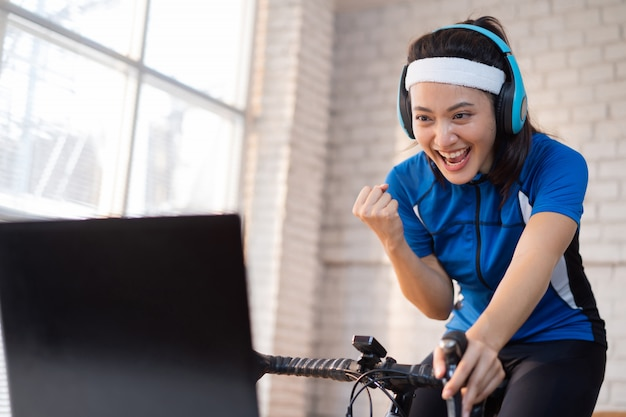 Ciclista mujer asiática. ella está haciendo ejercicio en la casa. al andar en bicicleta en el entrenador y jugar juegos de bicicleta en línea, ella está satisfecha
