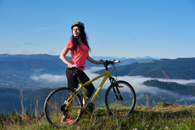 Ciclista de mujer atractiva con bicicleta amarilla en un sendero rural en las montañas, disfrutando de la bruma de la mañana en el valle, los bosques en el fondo borroso. actividad deportiva al aire libre