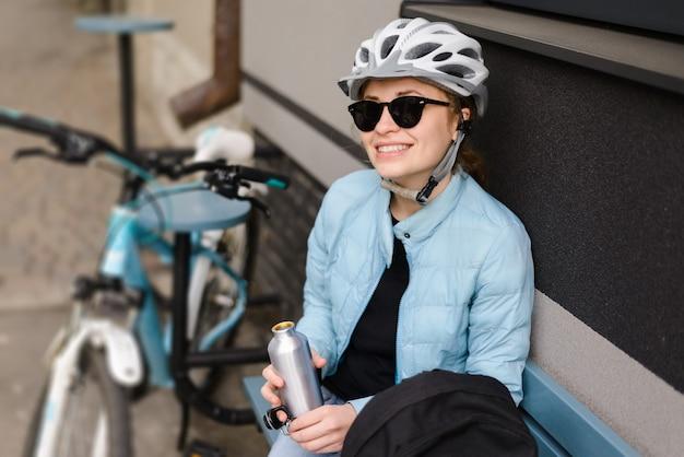 Ciclista de mujer en un casco y gafas de sol