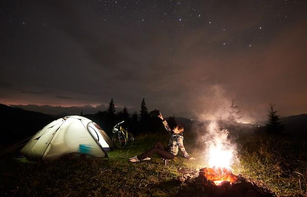 Ciclista de la mujer en la noche acampando cerca de una fogata ardiente
