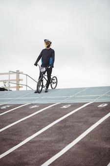 Ciclista de pie con bicicleta bmx en la rampa de inicio