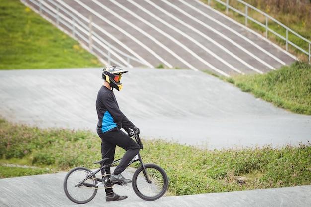 Ciclista de pie con bicicleta bmx