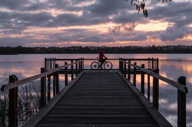 Ciclista de pie sobre un muelle de madera en el agua bajo un cielo nublado durante la puesta de sol por la noche