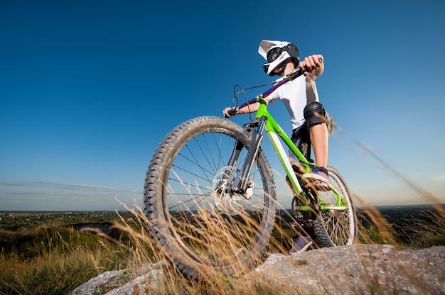 Ciclista preparándose para andar cuesta abajo en la bicicleta de montaña