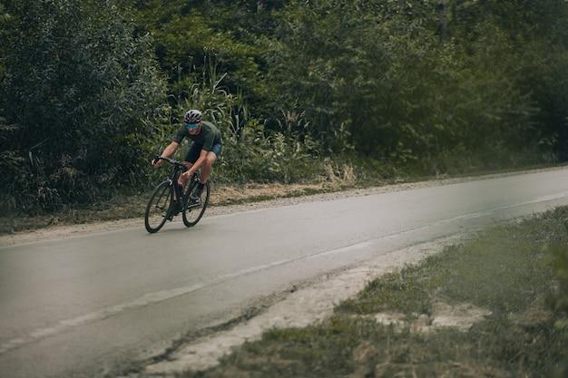 Ciclista profesional con casco de seguridad y gafas espejadas que tiene un entrenamiento intenso en bicicleta en la pista de pista entre el bosque. concepto de personas, deporte y estilos de vida saludables.