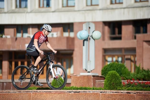 Ciclista profesional masculino montando bicicleta en el borde de la calle cerca de parterres y árboles en frente del edificio rojo.