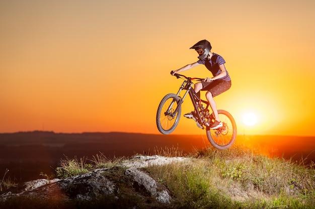 Ciclista que monta cuesta abajo en bicicleta de montaña en la colina