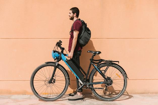 Ciclista urbano de pie junto a la bicicleta eléctrica.
