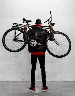 Ciclista urbano sosteniendo su bicicleta