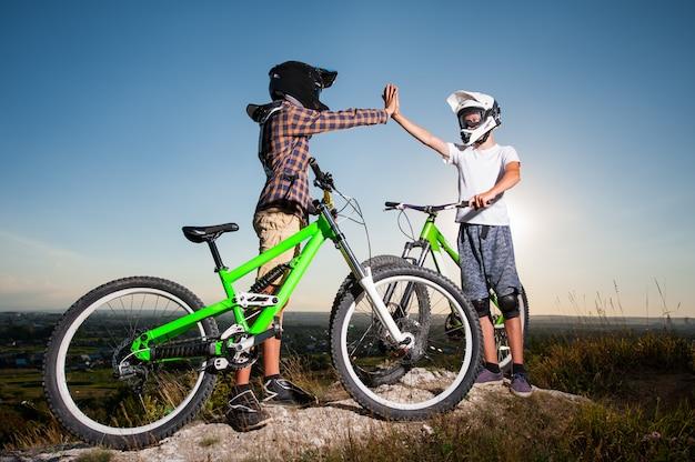 Ciclistas con bicicletas de montaña en la colina bajo un cielo azul