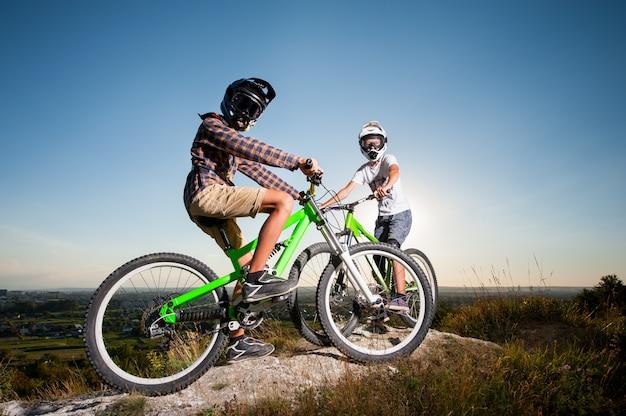 Ciclistas con bicicletas de montaña en la colina bajo el cielo azul