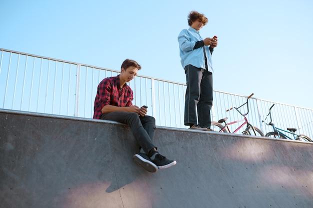 Ciclistas de bmx, adolescentes ocios en rampa en skatepark después del entrenamiento. deporte extremo en bicicleta, ejercicio de ciclo peligroso, paseos en la calle, ciclismo en el parque de verano
