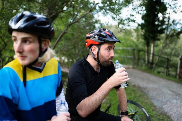 Ciclistas descansando y bebiendo agua en el bosque.