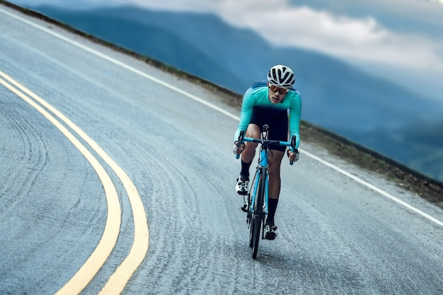 Los ciclistas están en bicicleta, escalando hasta la cima.
