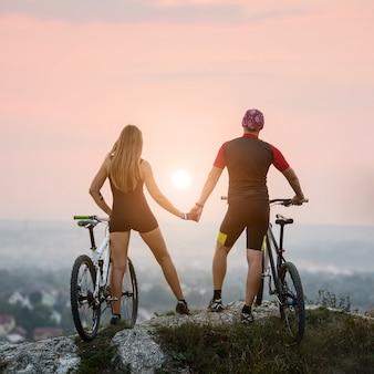 Ciclistas felices hombre y mujer con bicicletas de montaña en la cima de una colina, disfrutando de la puesta de sol