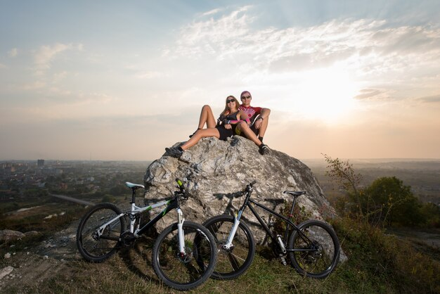 Ciclistas en piedra cerca de bicicletas deportivas
