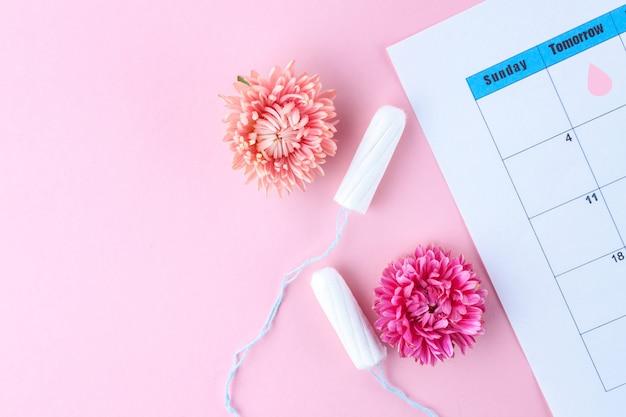 Ciclo menstrual regular. tampones, calendario de mujer, flores. cuidado de la higiene durante los días críticos. atención de salud femenina y ginecológica.